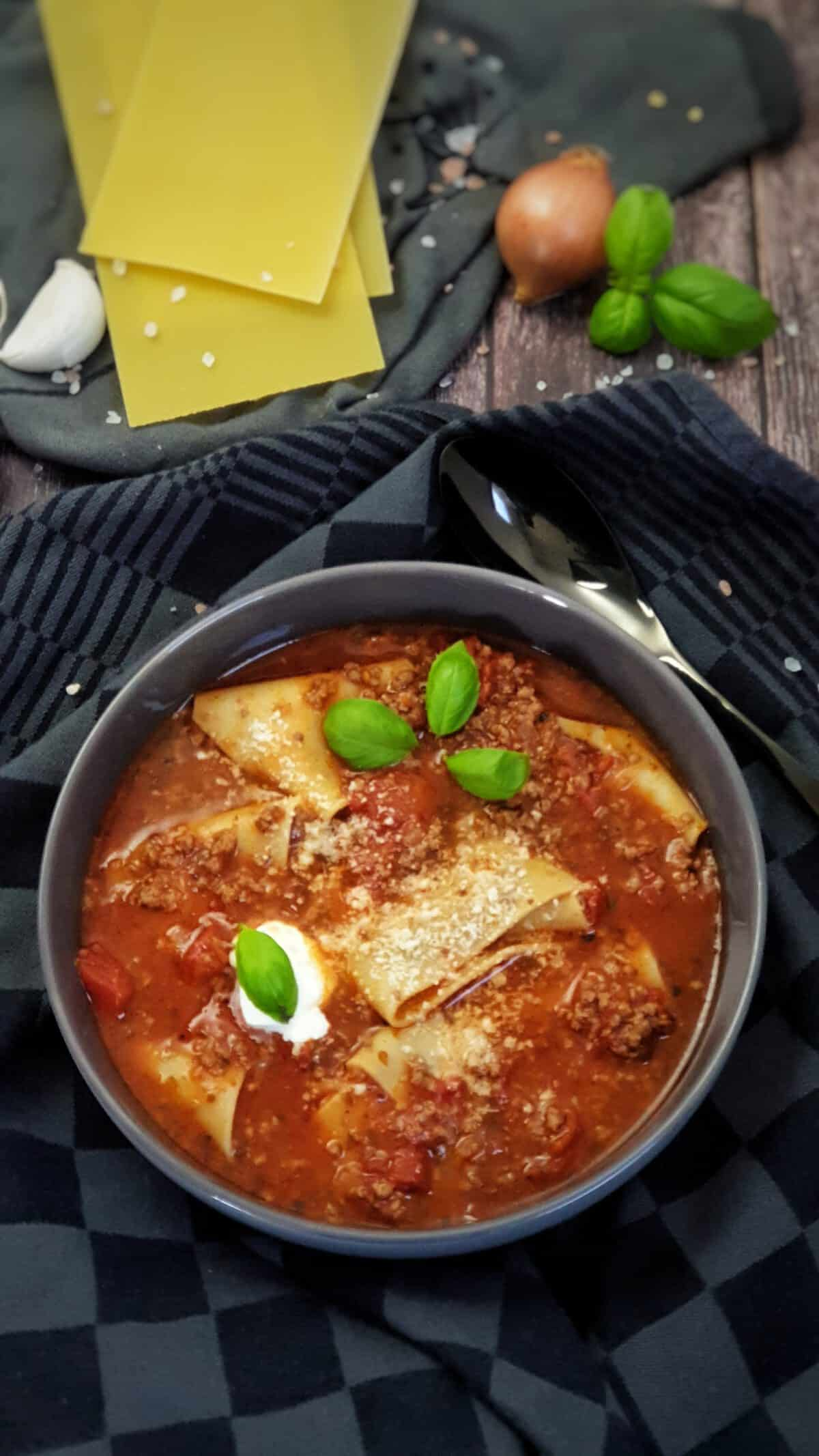 In einer grauen Schale angerichtet eine Lasagne-Suppe mit Hackfleisch. Im Hintergrund Deko.