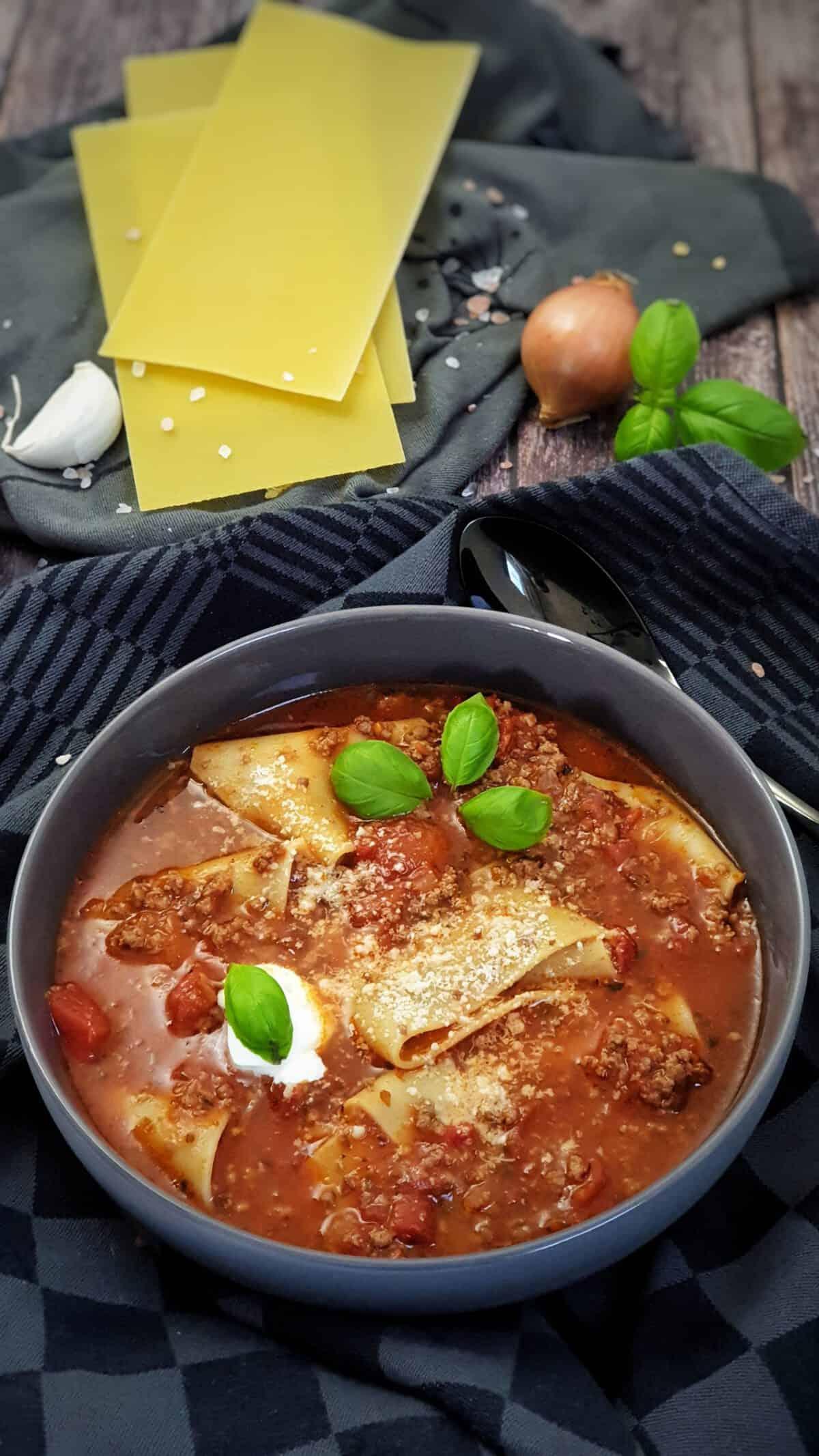 In einer grauen Schale angerichtet eine Suppe mit Hackfleisch und Lasagne-Platten. Im Hintergrund Deko.