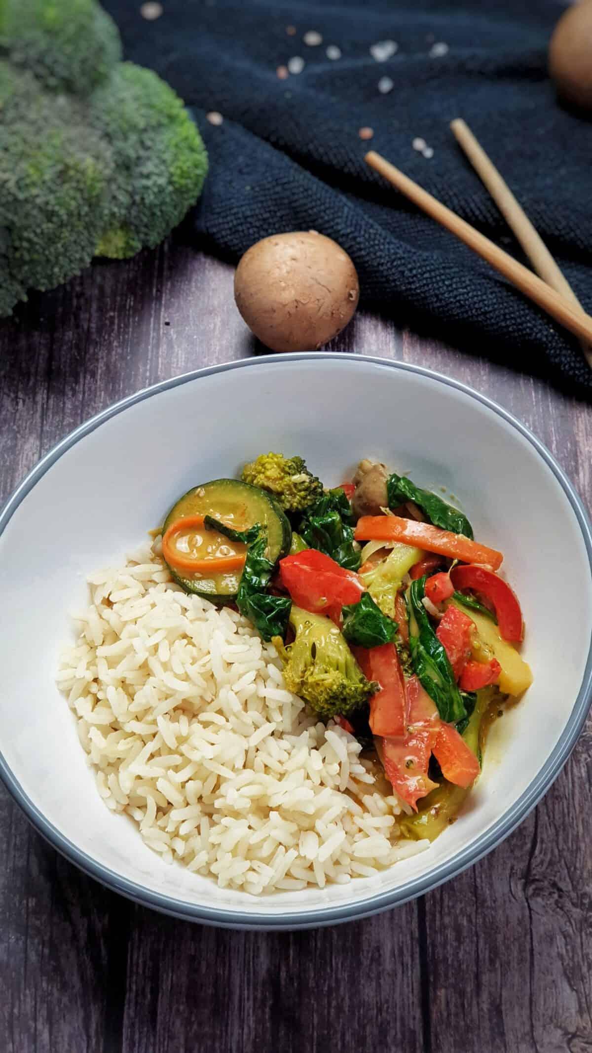 In einer weißen Schale Reis mit Gemüse-Curry in Kokosmilch angerichtet.