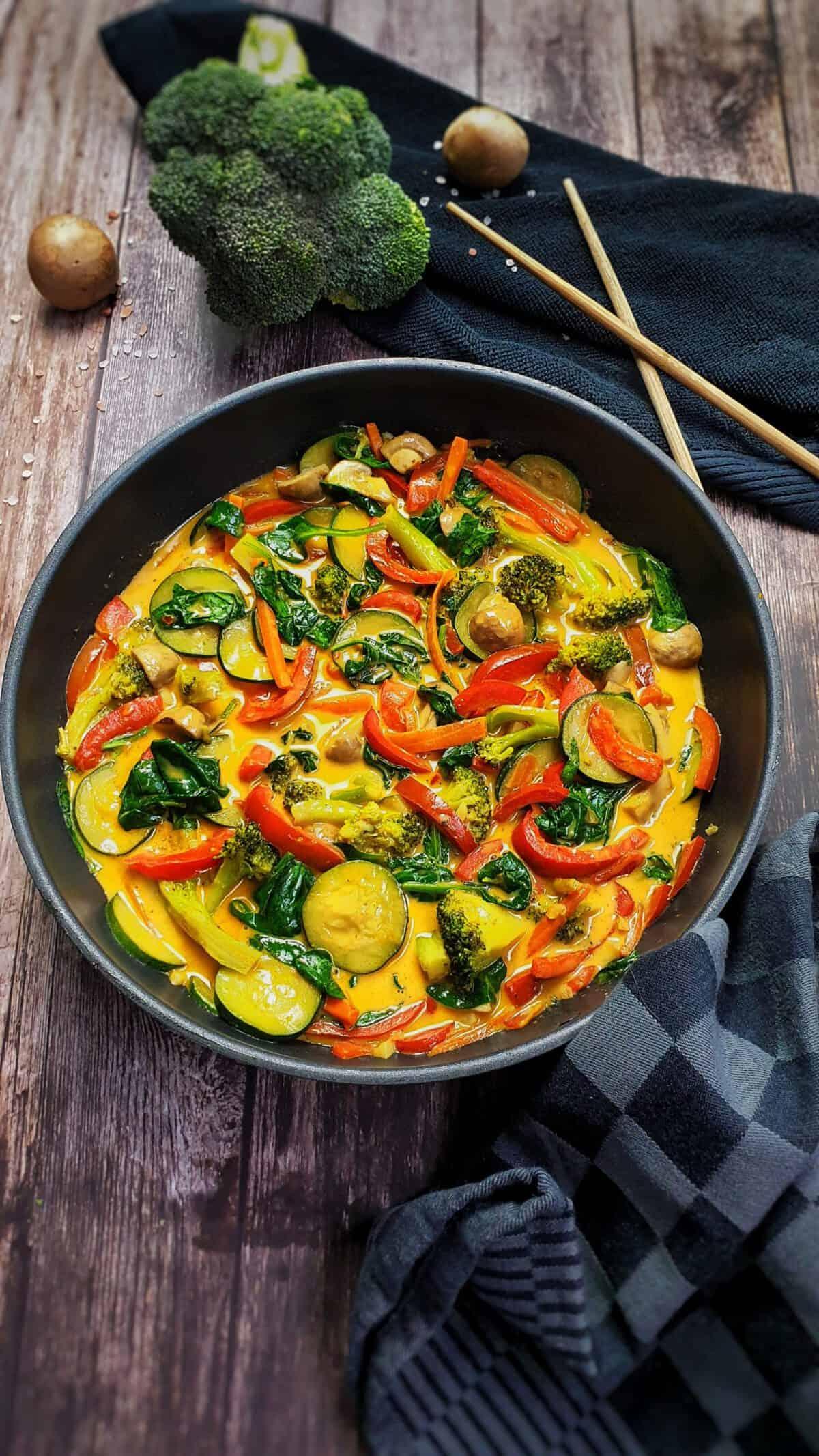 Gemüse-Curry mit Kokosmilch in der Pfanne serviert.