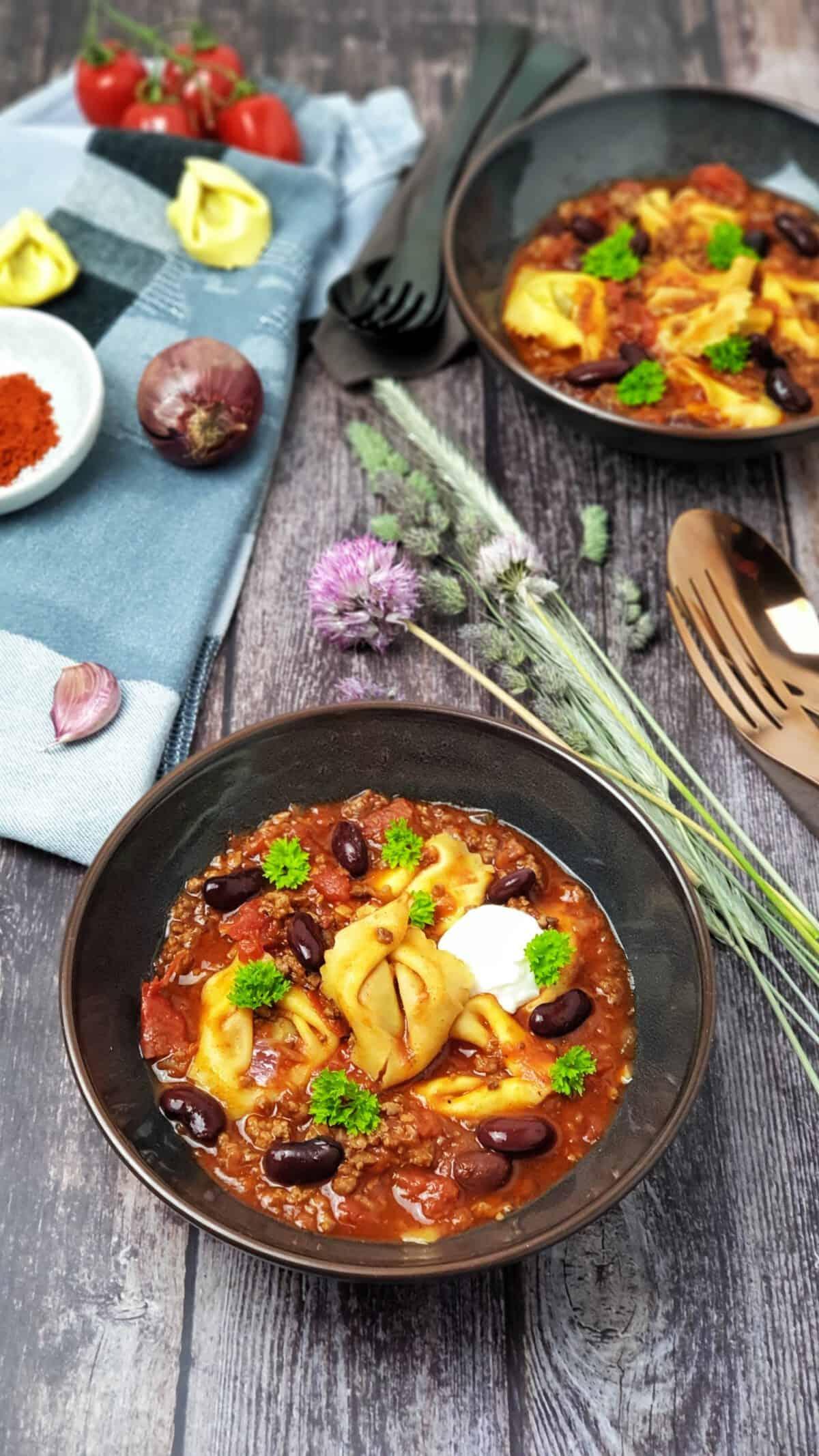 In einer braunen Schale serviert eine Tortellini-Suppe mit Hackfleisch. Mit Petersilie bestreut.