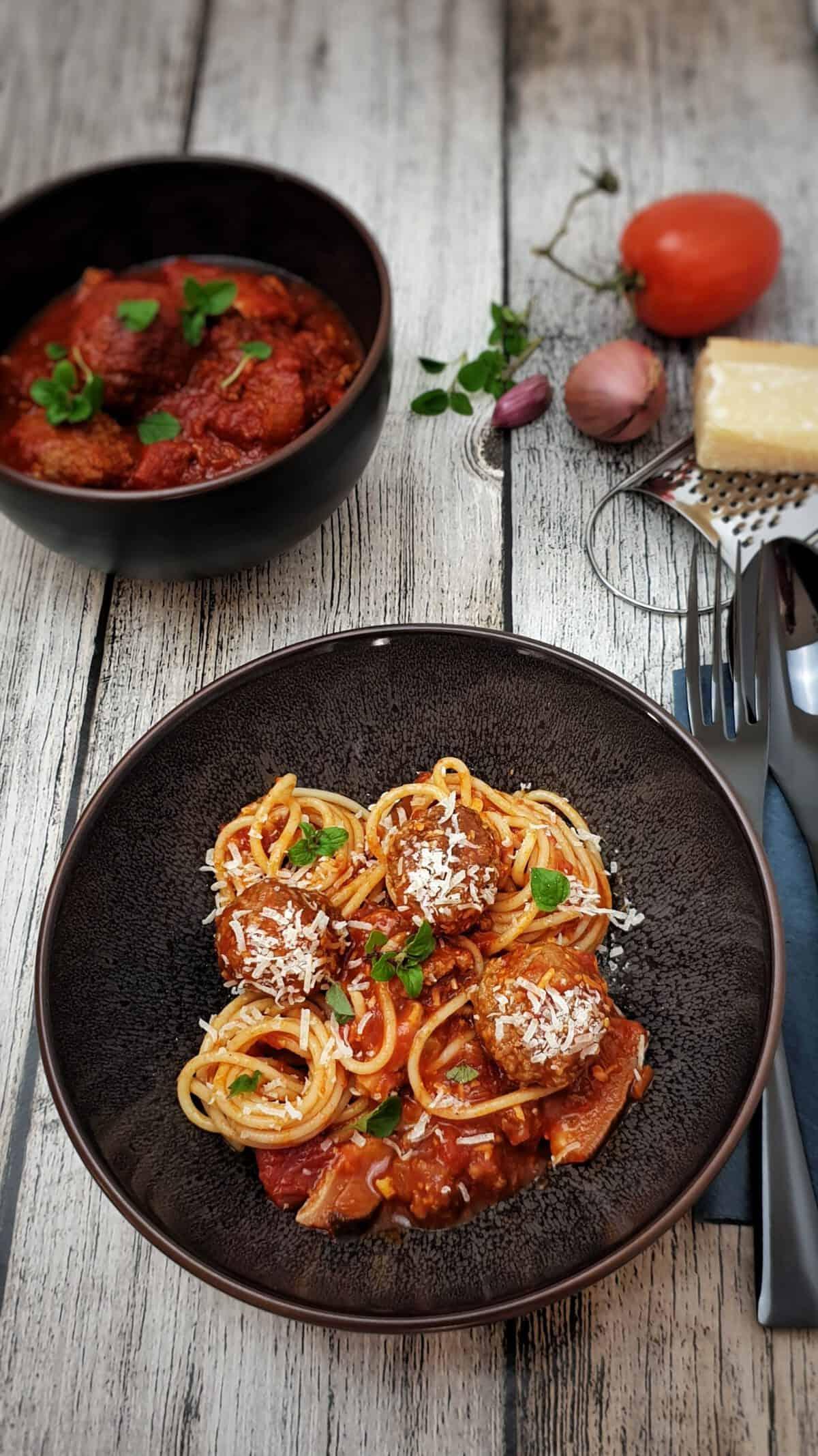 In einer braunen Schüssel Hackfbällchen mit Tomatensoße und Spaghetti. Serviert mit Parmesan und frischem Oregano.