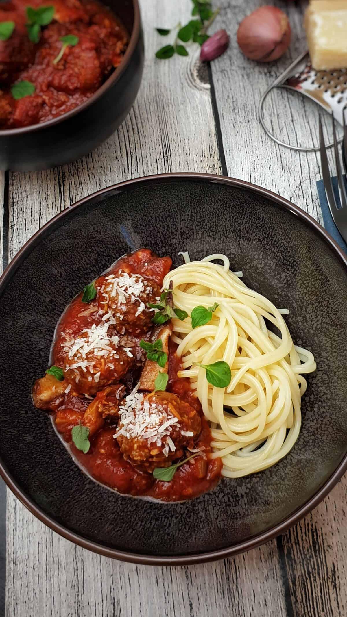 In einer braunen Schüssel Hackfleischbällchen mit Tomatensoße und Spaghetti. Serviert mit Parmesan und frischem Oregano.