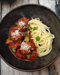 In einer braunen Schüssel Hackfleisch-Bällchen mit Tomatensoße und Spaghetti. Serviert mit Parmesan und frischem Oregano.