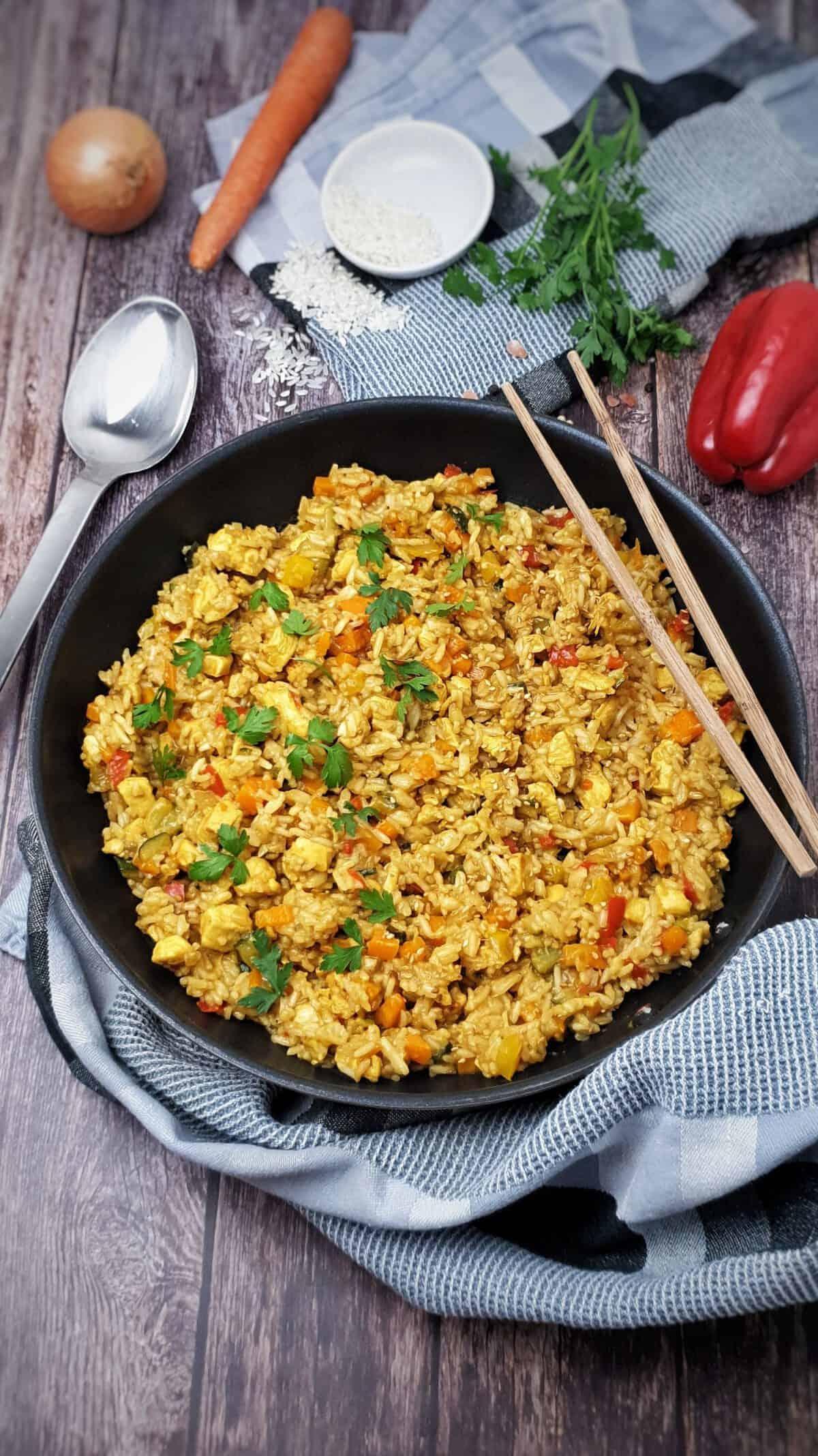 In einer Pfanne angerichtete und mit Petersilie bestreut eine asiatische Reispfanne mit Hähnchen. Im Hintergrund Deko.