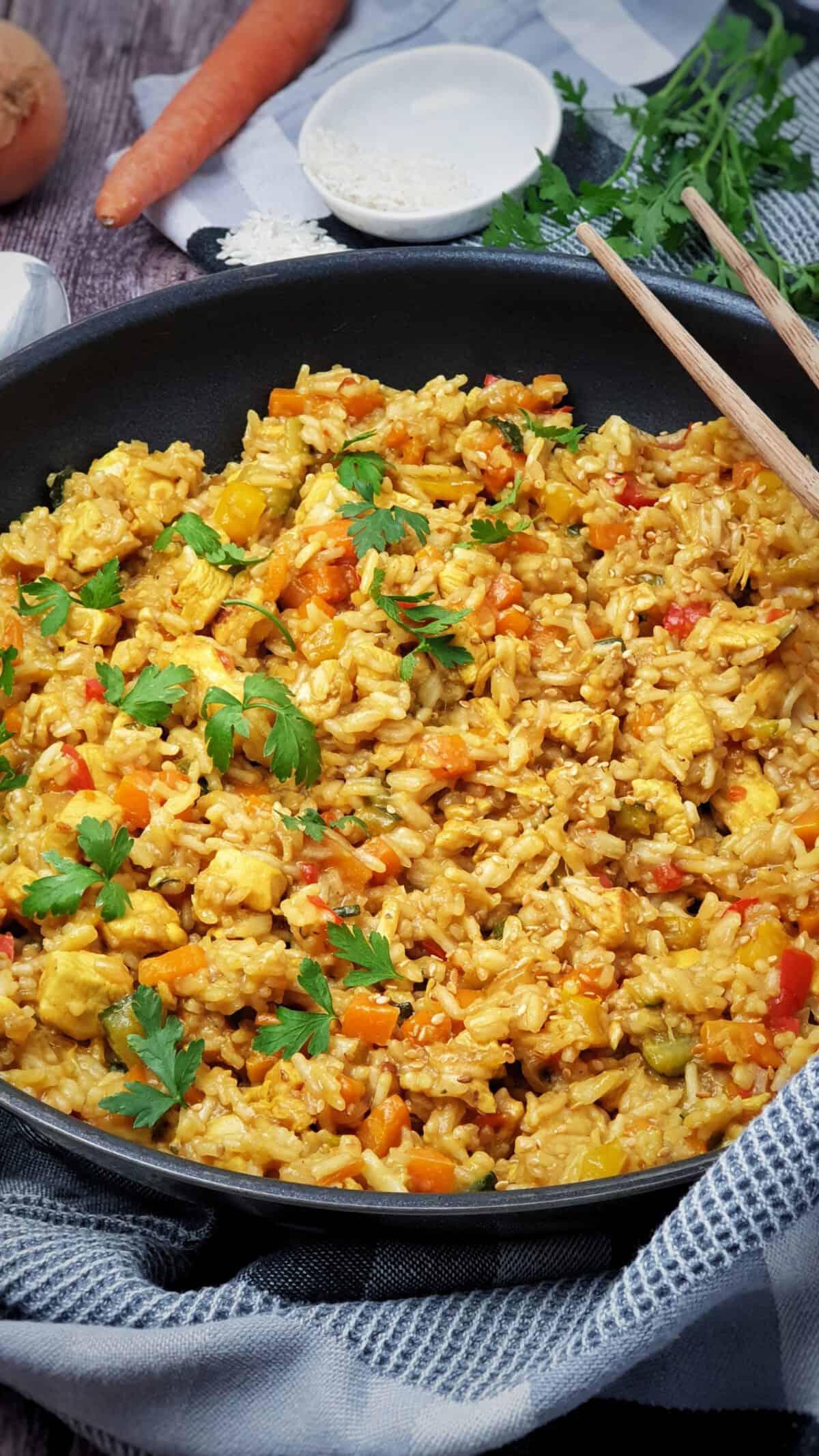 In einer Pfanne angerichtete und mit Petersilie bestreut eine asiatische Reis-Pfanne mit Hähnchen. Im Hintergrund Deko.
