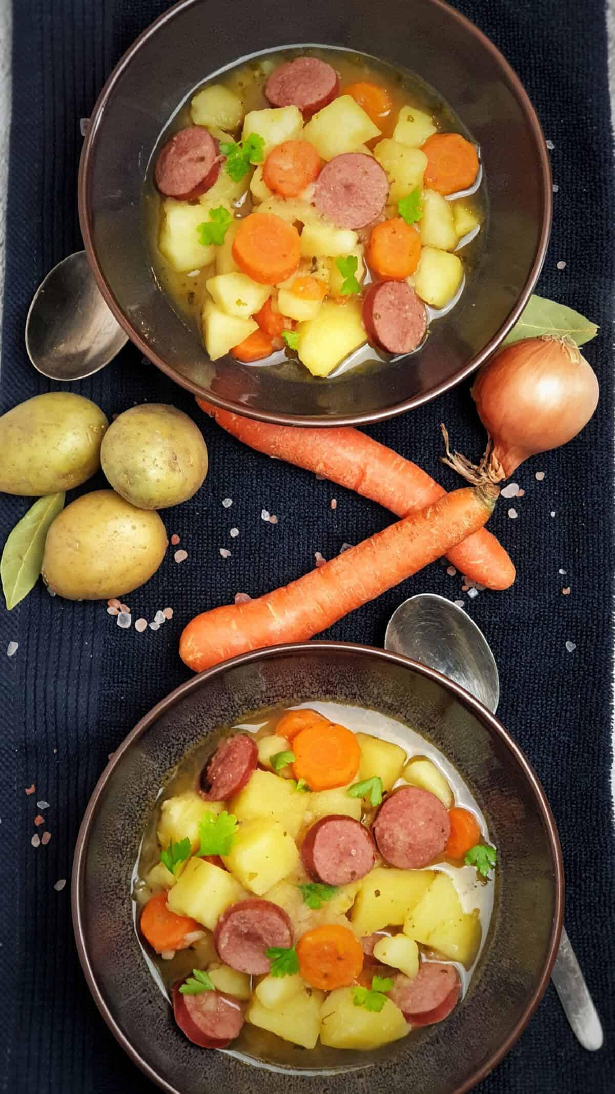 Zwei braune Schalen mit Kartoffel-Möhren-Eintopf mit Wurst auf einem Küchenhandtuch. Dazwischen Deko. Neben den Schalen Löffel.