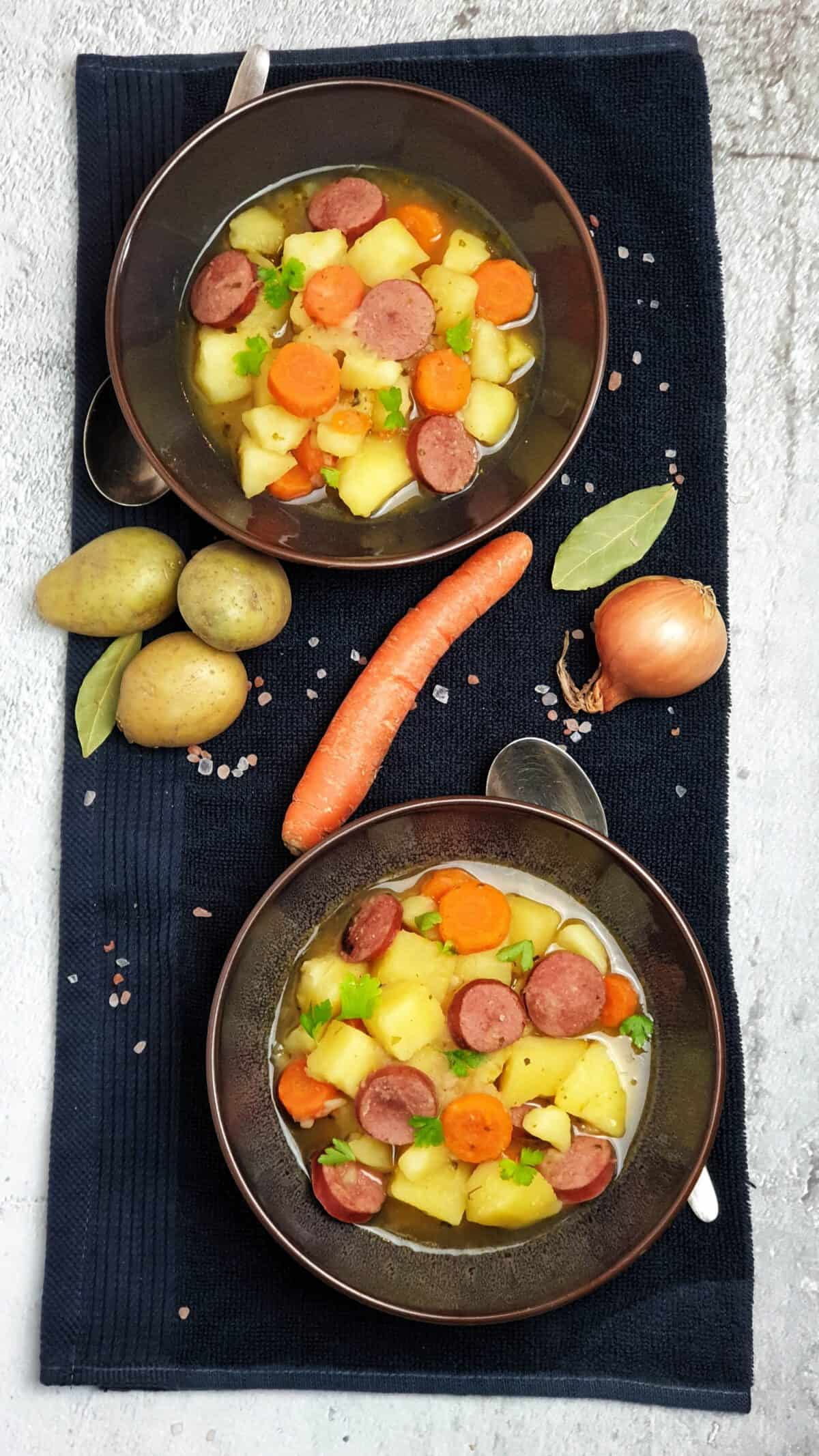Zwei braune Schalen mit Kartoffel-Möhren-Wurst Eintopf auf einem Küchenhandtuch. Dazwischen Deko. Neben den Schalen Löffel.