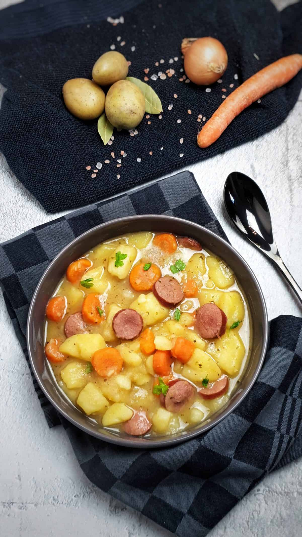 In einer grauen Schale angerichtet ein Kartoffel-Möhren Eintopf mit Wurst. Bestreut mit Petersilie. Im Hintergrund Deko.