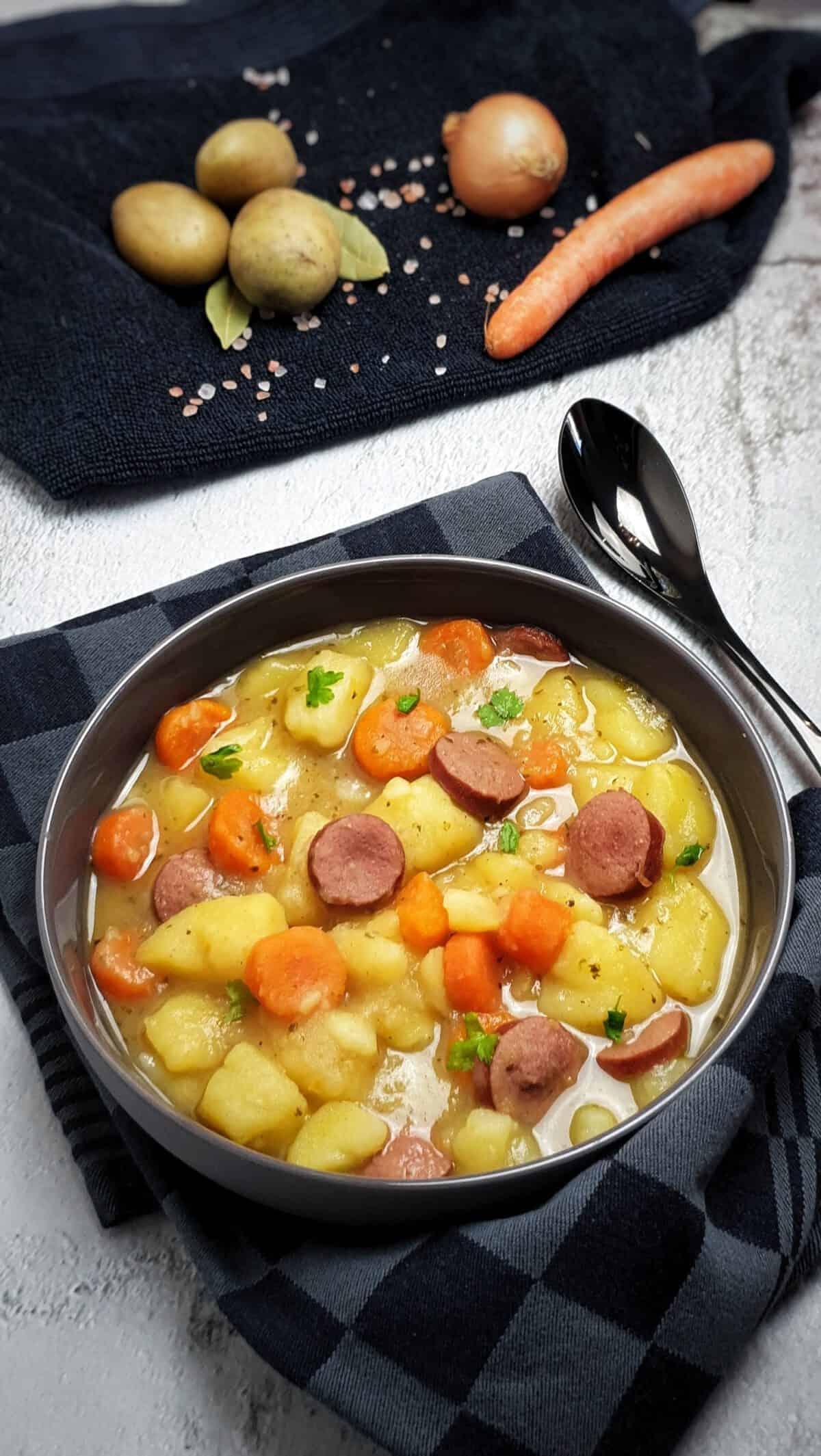 In einer grauen Schale angerichtet ein Kartoffel-Möhren-Eintopf mit Wurst. Bestreut mit Petersilie. Im Hintergrund Deko.