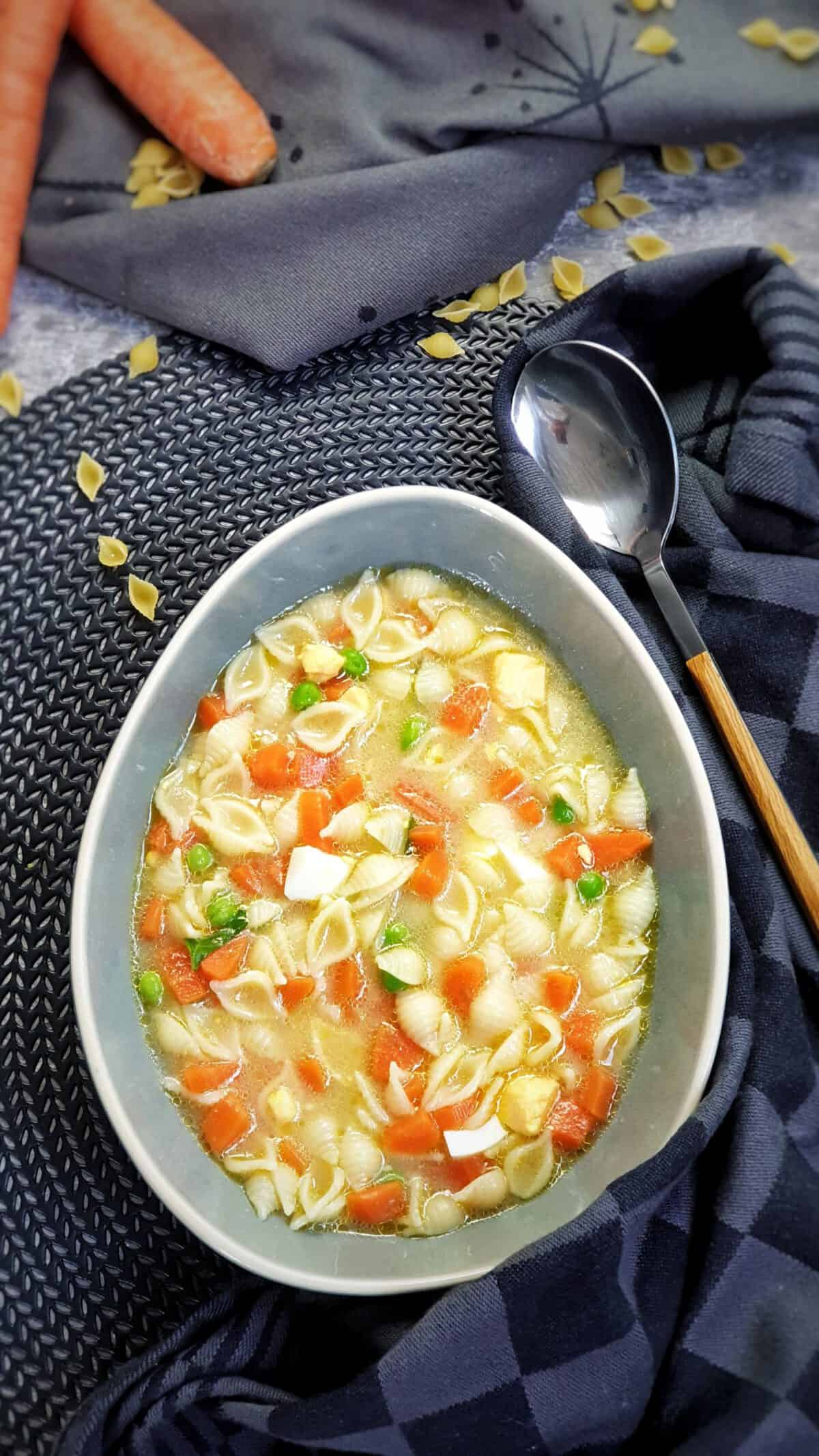 In einer graublauen Suppen Schale eine Nudel-Suppe mit Möhre und Ei.