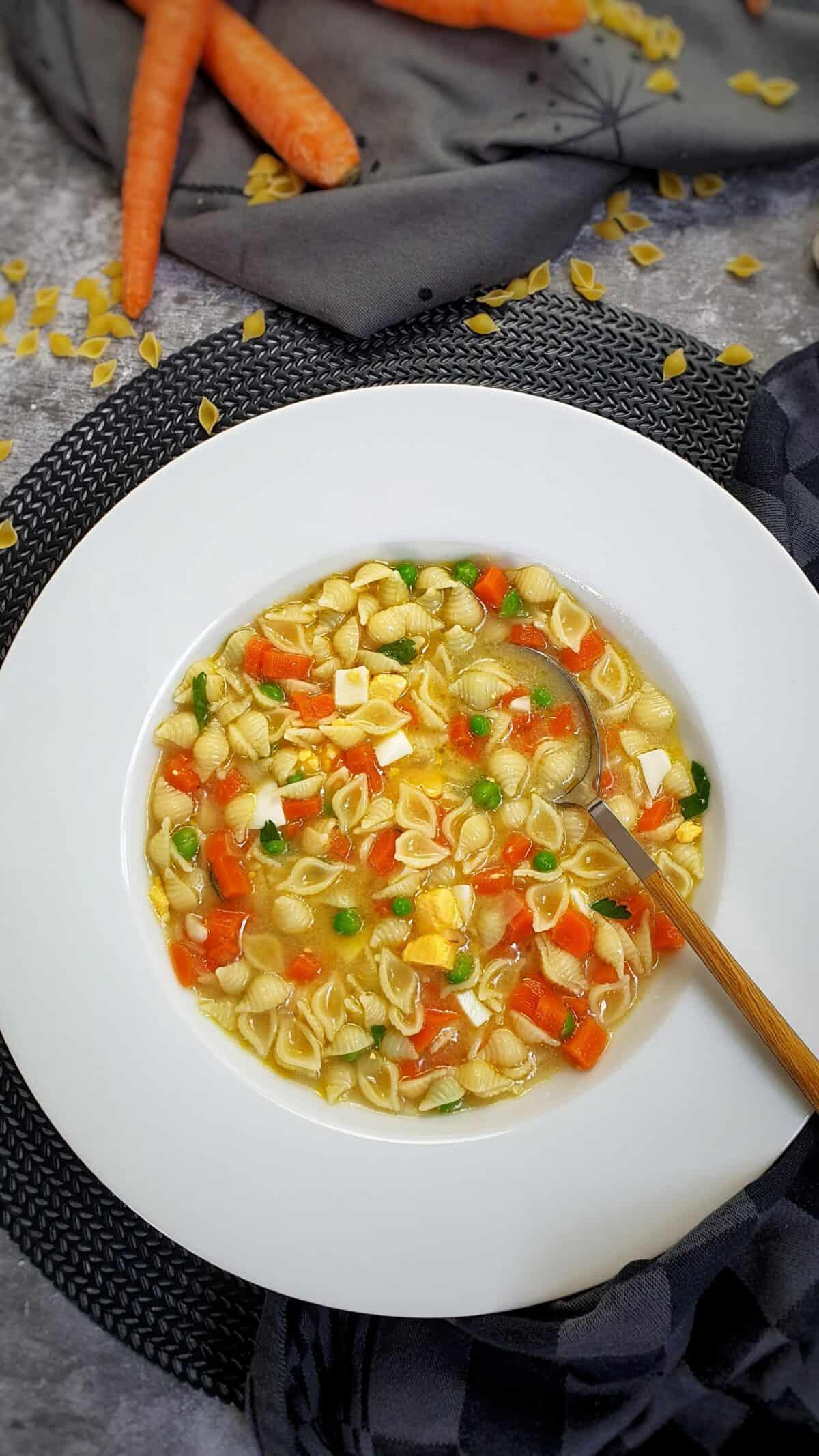 In einem weißen Suppenteller eine Nudel-Suppe mit Möhre und Ei. Im Hintergrund Deko.