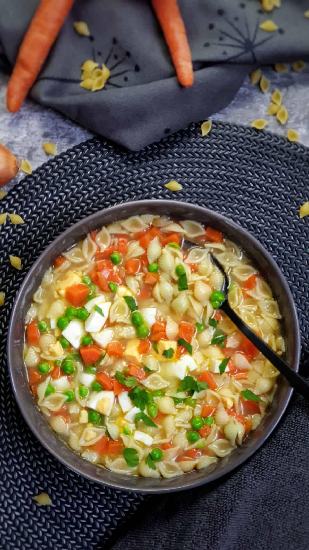 In einer grauen Suppen Schale eine Nudelsuppe mit Möhre und Ei.