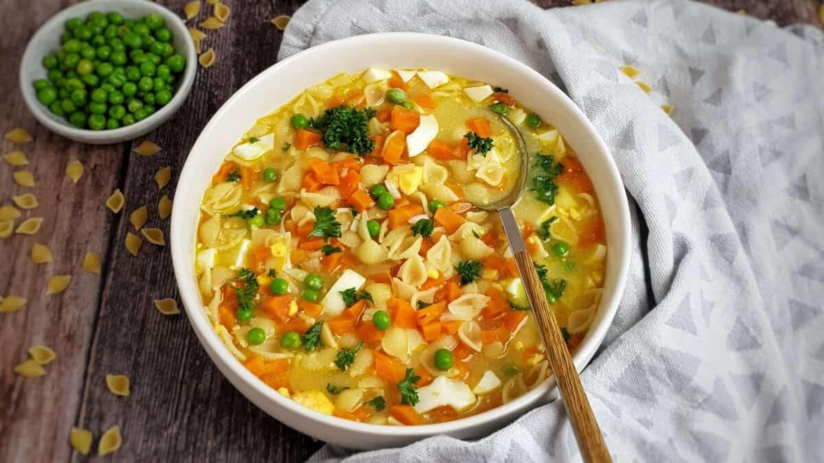In einer weißen Suppen Schale eine Nudelsuppe mit Möhre und Ei.