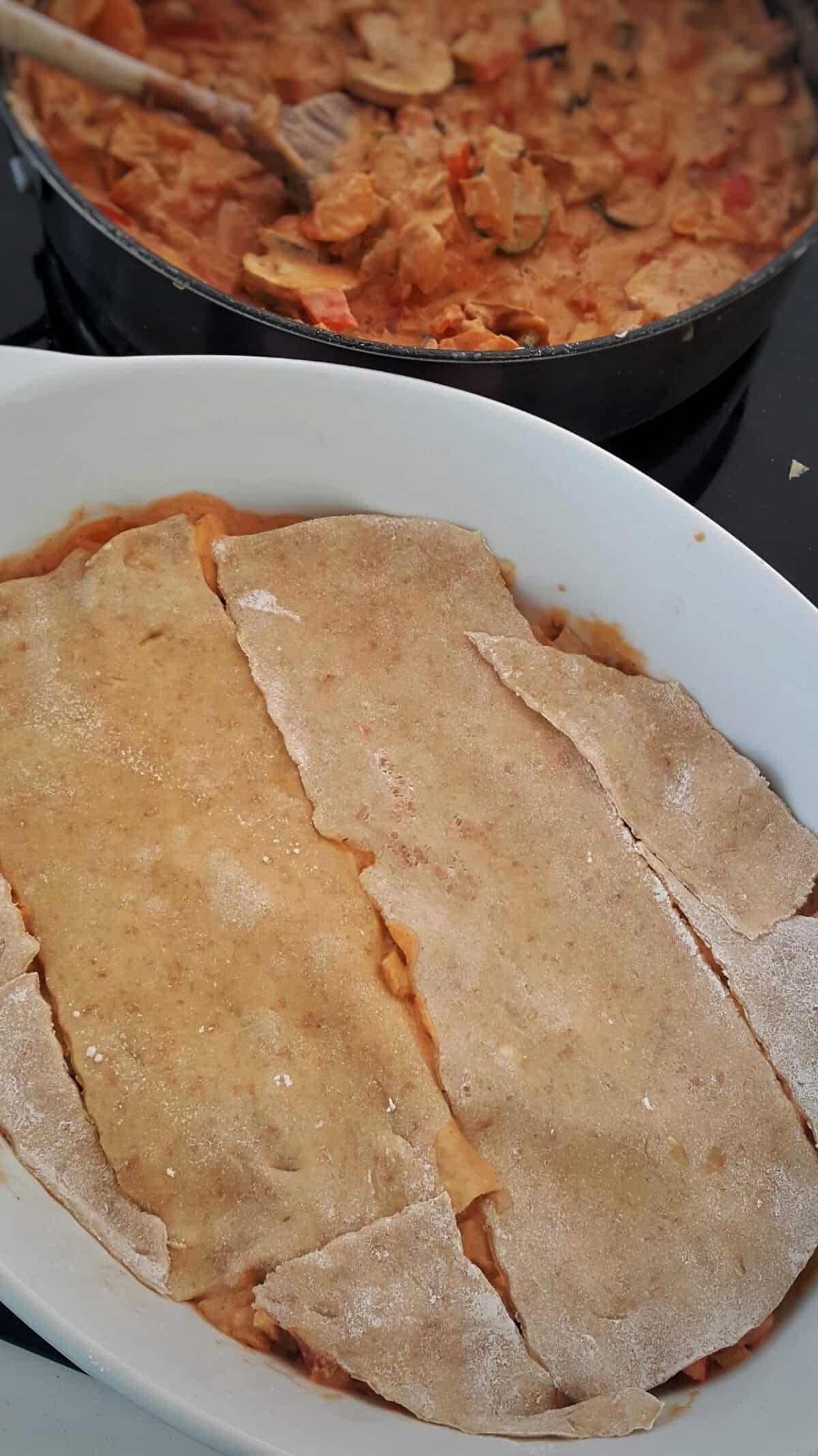 In einer weißen Auflaufform geschichtete Lasagne mit selbst gemachten Dinkel Lasagne Nudel Platten.