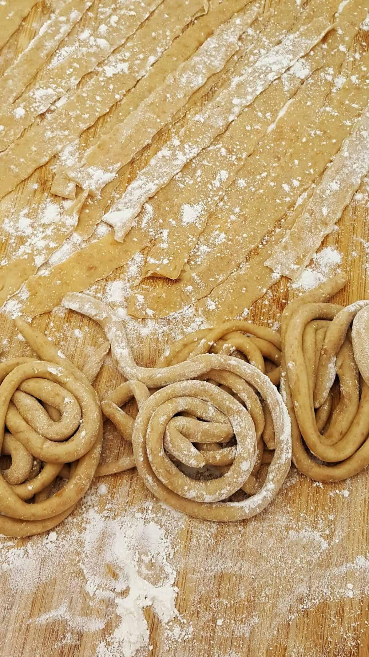 Auf einem Holz Schneidebrett selbst gemachte Dinkel Nudeln nach dem Grundrezept für Dinkel Nudel Teig in verschiedener Form.