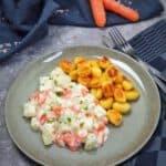 Auf einem grünen Teller Kohlrabi-Möhren-Gemüse mit Petersilie bestreut neben angebratenen Gnocchi.