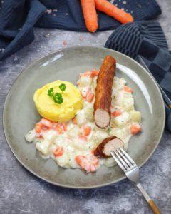 Auf einem grünen Teller Kohlrabi-Möhren Gemüse mit Petersilie bestreut neben Kartoffelpüree. Auf dem Gemüse eine Bratwurst.