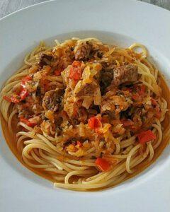 In einem weißen Teller angerichtet Laghman mit Spaghetti.