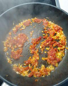 In einer Pfanne angedünstete Zwiebeln mit Öl und geröstetes Tomatenmark.