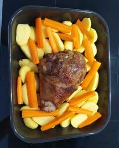 In einer schwarzen Auflaufform eine Putenkeule auf Kartoffeln und Möhren.