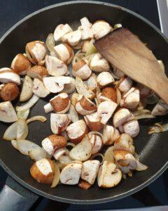 In einer Pfanne angebratene Pilze mit Zwiebeln und Knoblauch.