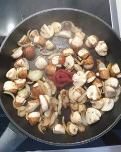 In einer Pfanne angeratene Pilze mit Tomatenmark.