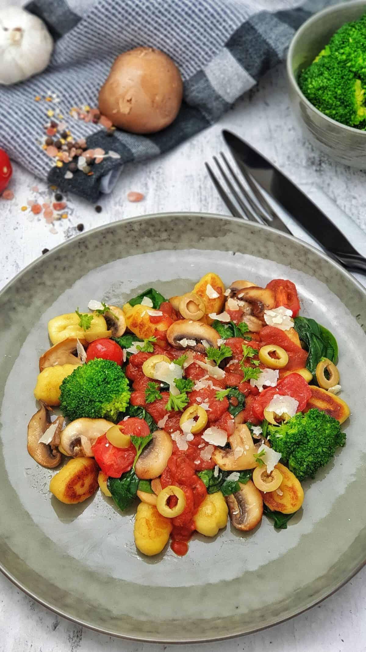 Gnocchi mit Tomatensoße und Gemüse auf einem grünen Teller angerichtet.