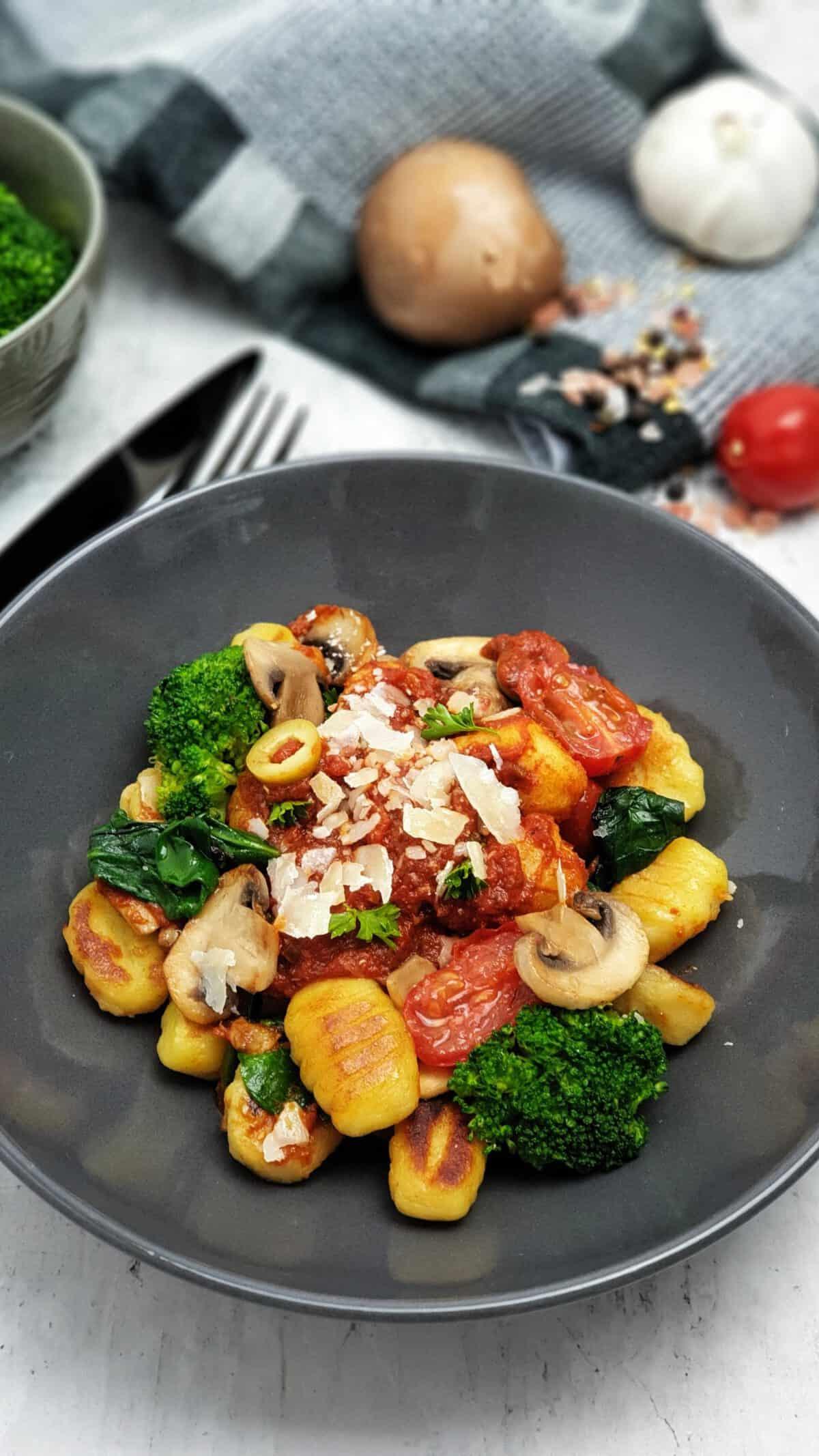 Gnocchi mit Tomatensoße und Gemüse in einer grauen Schale angerichtet.