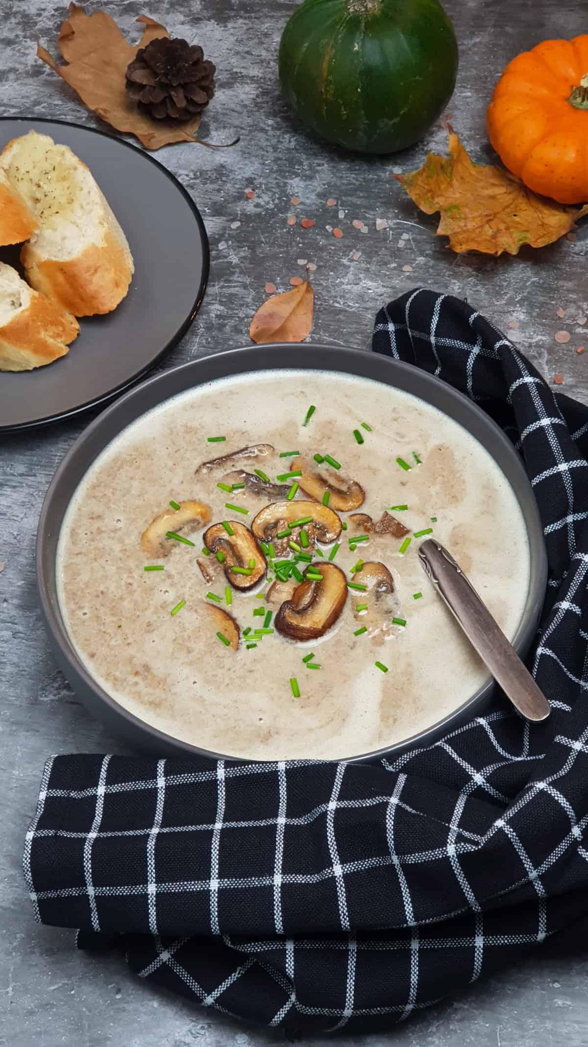 Pilz-Creme-Suppe mit Champignons in einer grauen Schale serviert. Mit Schnittlauch bestreut. Im Hintergrund Herbst Deko.
