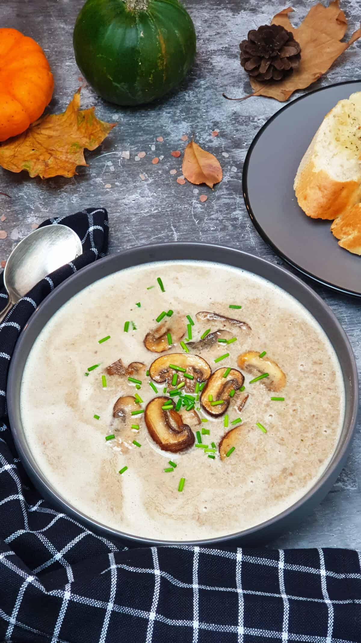 Pilz Creme Suppe mit Champignons in einer grauen Schale serviert. Mit Schnittlauch bestreut. Im Hintergrund Herbst Deko.
