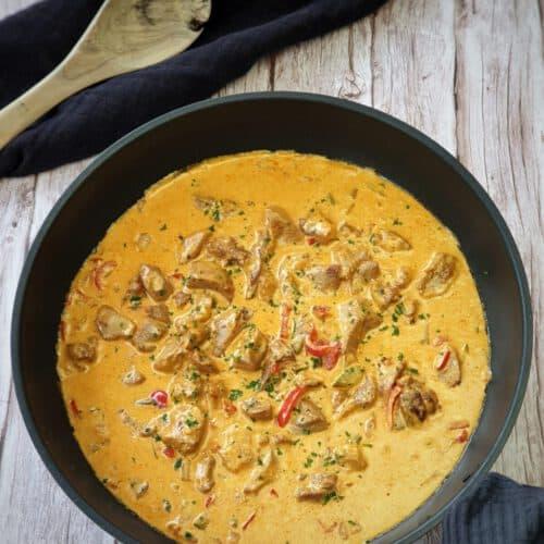 In einer schwarzen Pfanne Puten-Gulasch mit Paprika und Zucchini, Bestreut mit frischer Petersilie. Im Hintergrund Deko.