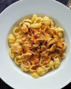 In einem weißen Pasta Teller Gnocchi Nudeln mit Putengulasch.
