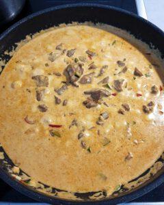 In einer Pfanne auf dem Herd kocht ein Putengulsch mit Paprika und Zucchini.