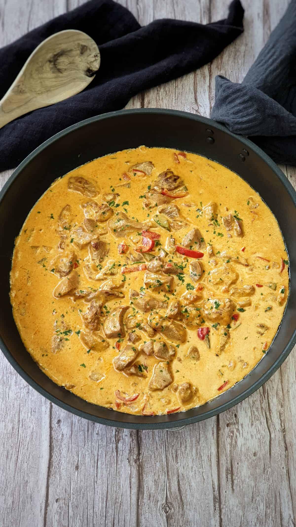 In einer schwarzen Pfanne Putengulasch mit Paprika und Zucchini, Bestreut mit frischer Petersilie. Im Hintergrund Deko.