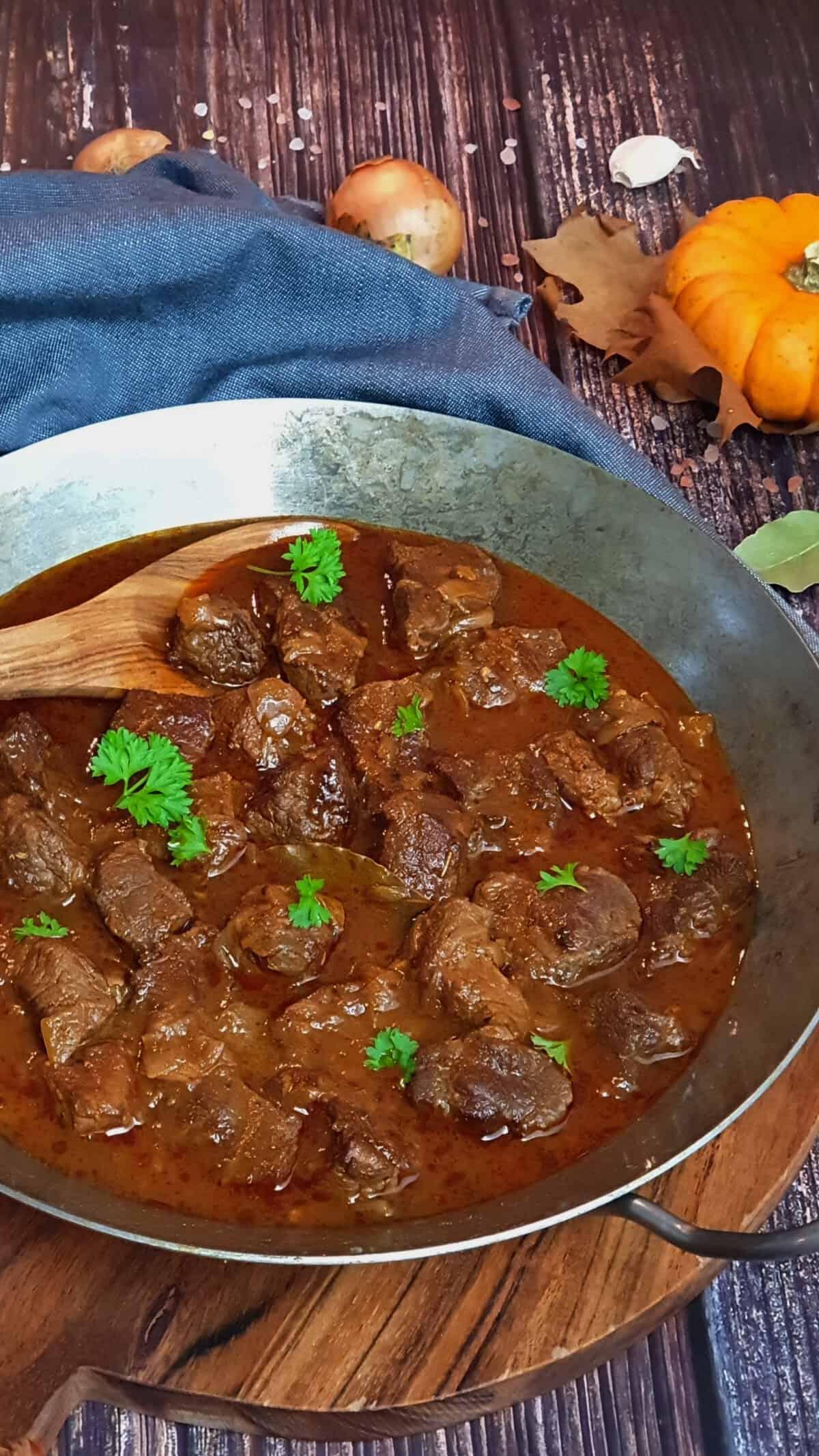 In einer gußeisernen Pfanne ein Gulasch mit Rindfleisch. Mit Petersilie garniert. Im Hintergrund Deko.