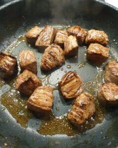 Angebratenes Rindfleisch in Öl in einer Pfanne.