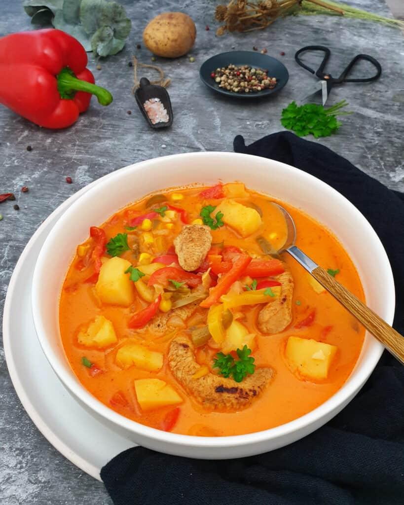 In einer weißen runden Schale eine Suppe mit Fleisch, Kartoffeln, Paprika und Mais. Im Hintergrund Deko.