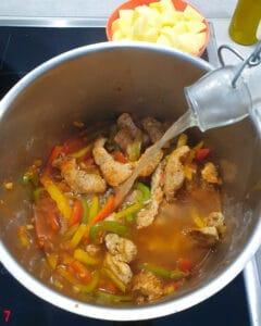 In einem Topf Angebratenes Fleisch und angedünstete Paprika mit Brühe.