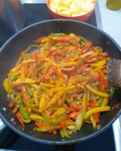 In einer Pfanne angedünstete bunte Paprika in Streifen.