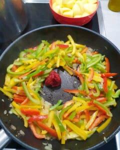In einer Pfanne angedünstete Paprika mit Zwiebeln und Tomatenmark.