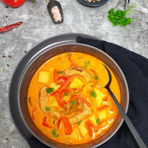 In einer grauen Schale angerichtet Gyrossuppe mit Kartoffeln, Hähnchen und Paprika. Im Hintergrund Deko.
