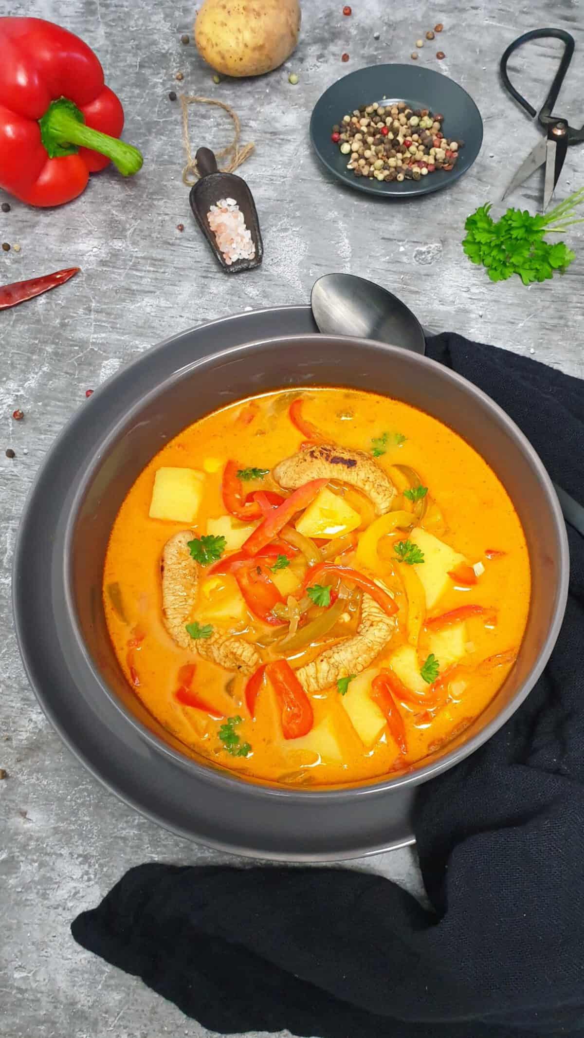 In einer grauen Schale eine Suppe mit Gyros-Fleisch, Paprika und Kartoffeln. Im Hintergrund Deko.
