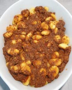In einer weißen Auflaufform angebratene Gnocchi mit Bolognese Soße.