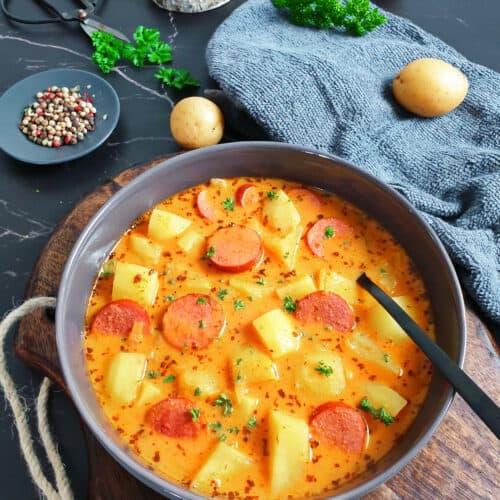 In einer grauen Schale Kartoffelgulasch mit Würstchen. Bestreut mit frischer Petersilie. Im Hintergrund Deko.