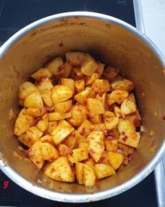 In einem Topf in Würfel geschnittene Kartoffeln mit Tomatenmark angeröstet.