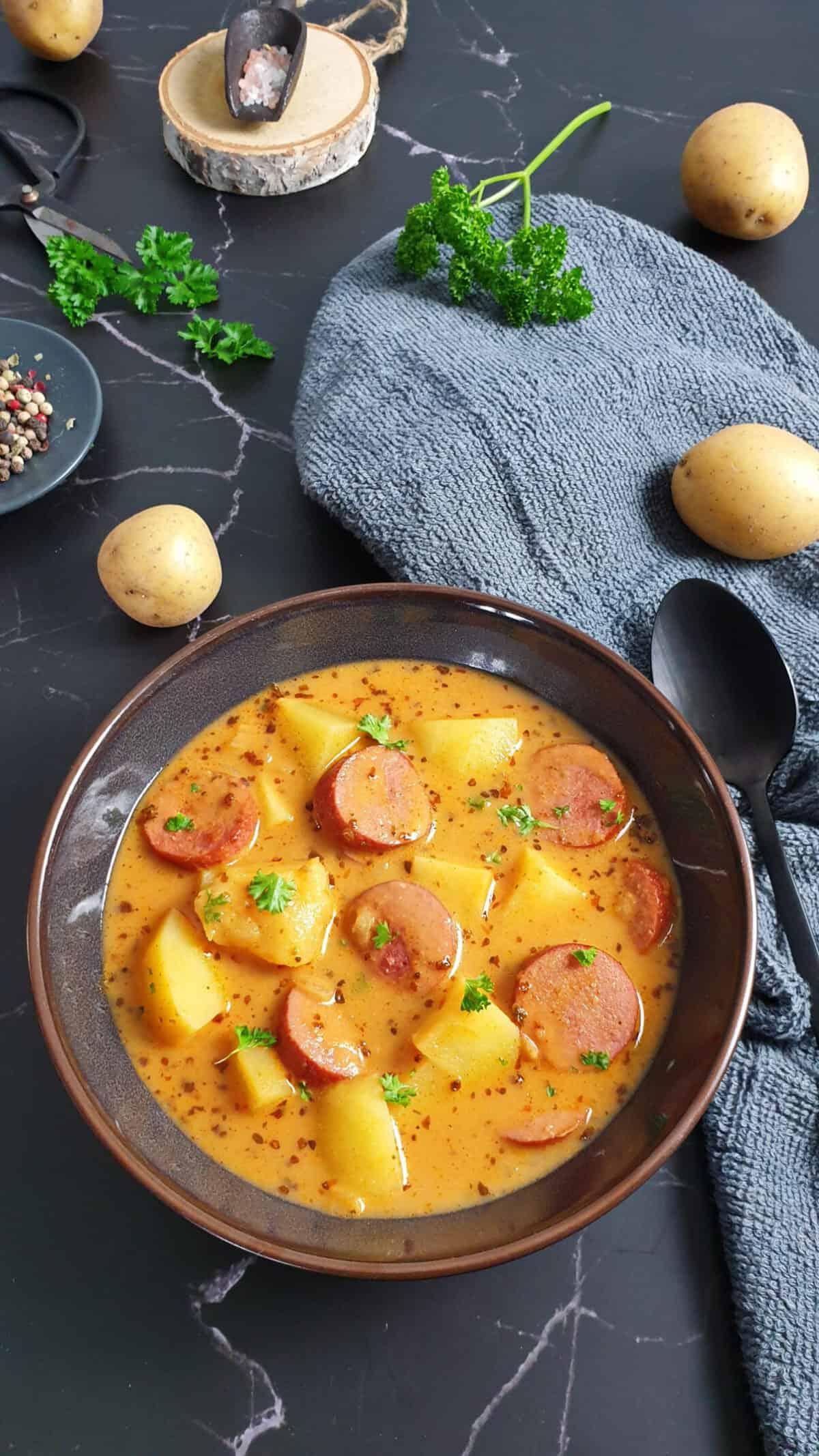 In einer braunen Schale Kartoffel-Gulasch mit Würstchen. Bestreut mit frischer Petersilie. Im Hintergrund Deko.