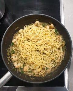 In einer Pfanne Spaghetti mit Garnelen und Kräuterbutter.
