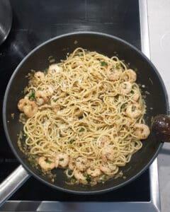In einer Pfanne Spaghetti mit Garnelen und Parmesan Käse.