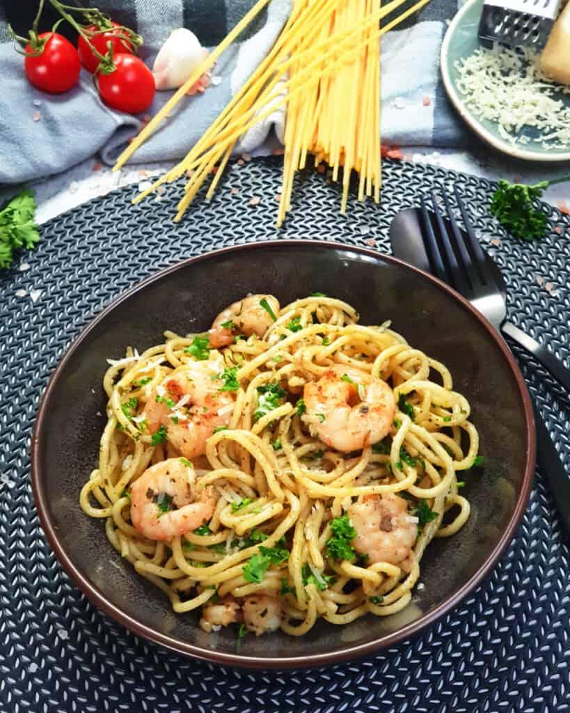 In einer braunen Schale Spaghetti mit Garnelen in Kräuterbutter. Im Hintergrund Deko.